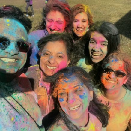 7 smiling people covered in holi colored powders taking a selfie.